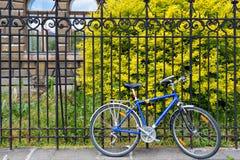 Support bleu de bicyclette sur la serrure à la barrière grunge en métal Rue européenne Bicyclette moderne Image stock