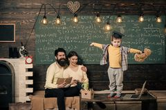 Support concept. Kid holds teddy bear and performing. Boy presenting his knowledge to mom and dad. Parents listening. Their son, chalkboard on background. Smart royalty free stock photography