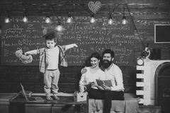 Support concept. Kid holds teddy bear and performing. Boy presenting his knowledge to mom and dad. Parents listening. Their son, chalkboard on background. Smart royalty free stock photos