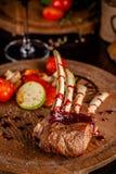 Support d'agneau avec les légumes et la sauce grillés à framboise Plats de portion sur un conseil en bois avec un verre de vin ro images libres de droits