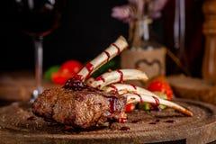 Support d'agneau avec les légumes et la sauce grillés à framboise Plats de portion sur un conseil en bois avec un verre de vin ro photo stock