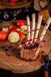 Support d'agneau avec les légumes et la sauce grillés à framboise Plats de portion sur un conseil en bois avec un verre de vin ro image stock