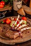 Support d'agneau avec les légumes et la sauce grillés à framboise Plats de portion sur un conseil en bois avec un verre de vin ro photographie stock