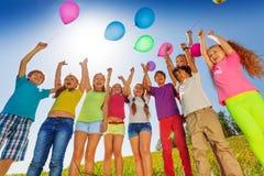 Support d'enfants dans le demi-cercle avec des ballons  Images stock