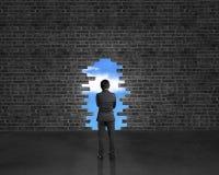 Support d'homme d'affaires vis-à-vis le grand trou sur le mur de briques dans le pl foncé Images stock