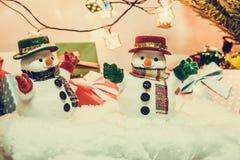 Support de bonhomme de neige parmi la pile de la neige la nuit silencieux avec une ampoule, un Joyeux Noël et une nuit de nouvell Images libres de droits