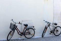 Support de deux bicyclettes à un mur blanc Photo libre de droits