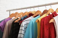 Support de garde-robe avec les vêtements élégants sur le fond blanc photographie stock