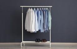 Support de garde-robe avec les vêtements des hommes images stock