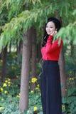 Support de jeune femme sur la forêt et écouter la musique avec des écouteurs photos libres de droits