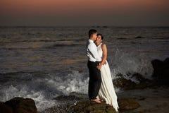 Support de jeunes mariés sur la plage Images stock