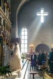 Support de jeunes mariés vis-à-vis de l'iconostase dans les rayons de la lumière Image stock