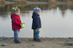Support de jumeaux près du lac avec des seaux Images libres de droits