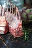 Support de l'agneau, viande crue avec l'os sur la table de cuisine rustique au fond en bois, vue de côté photographie stock