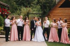 Support de marié et de jeune mariée avec le garçon d'honneur et la demoiselle d'honneur dehors Nouveaux mariés embrassant et appl photos stock