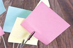 Support de note avec les notes collantes colorées sur le fond en bois Photographie stock libre de droits