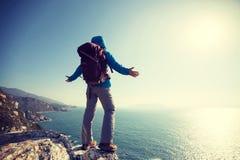 support de randonneur sur le bord de falaise de montagne de bord de la mer de lever de soleil Photographie stock libre de droits
