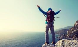 support de randonneur sur le bord de falaise de montagne de bord de la mer de lever de soleil Photos libres de droits