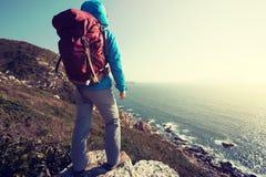 support de randonneur sur le bord de falaise de montagne de bord de la mer de lever de soleil Image stock