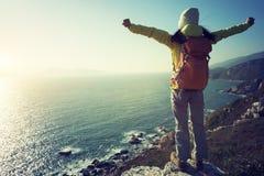 support de randonneur sur le bord de falaise de montagne de bord de la mer de lever de soleil Images stock