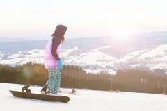 Support de surfeur de fille sur le fond des montagnes couronnées de neige, se préparant au slalom Article de sport moderne pour d image stock