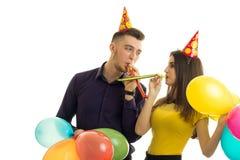 Support drôle de type et de fille vis-à-vis de l'un l'autre klaxons de coup et ballons multicolores de transport Images stock