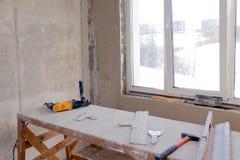 Support en bois d'échafaudage à la fenêtre dans une grande salle vide, réparation, plâtrant, murs de peinture, outils de bâtiment photos libres de droits