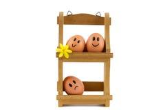 Support en bois d'oeufs avec trois oeufs avec des expressions du visage Photographie stock libre de droits