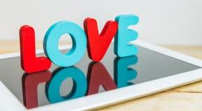 Support en bois de mot AMOUR sur le comprimé Image stock