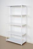 Support en métal blanc près du mur, étagères vides Photographie stock