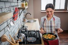 Support gentil gai de femme dans la cuisine au fourneau Elle tiennent la poêle avec la nourriture dans elle Sourire et regard mod photo stock
