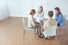 Support group during classes. Female psychotherapist with support group during classes stock photos
