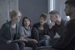 Support group meeting with psychologist. Support group meeting with female psychologist in a dark room Royalty Free Stock Photos