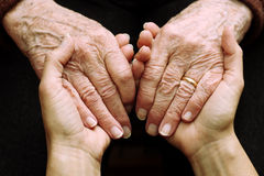 Support and help the elderly. Hands of the elderly woman in the foreground welcomed and supported by the hands of young woman Royalty Free Stock Photography