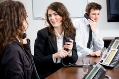 Support helpdesk. Young customer service operator team working at office, holding phone, calling, giving helpdesk support Stock Photo