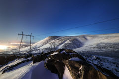 Support of the high-voltage line. A winter night mountain landscape Royalty Free Stock Photography