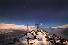 Support of the high-voltage line. A winter night mountain landscape Stock Photos