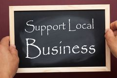 Support Local Business. Hands holding blackboard with the text Support Local Business. Business concept stock photo