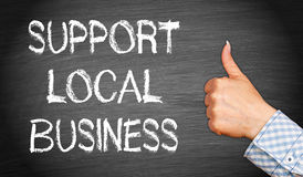 Support local business. Woman's hand giving thumbs up next to blackboard with graphic text support local business in white chalk royalty free stock image