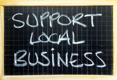 Support Local Business. The words Support Local Business written by hand in white chalk on a blackboard as a reminder to buy goods and services in your community Stock Photos