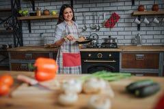 Support magnifique gentil de femme dans la cuisine et le sourire Elle tiennent la poêle avec la nourriture et la mélangent à la c images libres de droits