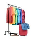 Support mobile avec des vêtements colorés et une valise sur le fond blanc Le fichier contient un chemin à l'isolement Images stock