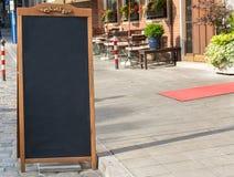 Support noir de tableau sur le bois pour un menu de restaurant dans le stre Photographie stock libre de droits