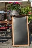 Support noir de tableau sur le bois pour un menu de restaurant dans le stre Photo stock