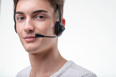 Support phone call center operator in headset. Contact us concept - Support phone call center operator young man in headset looking at camera and smiling with stock photography