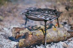 Support pour la bouilloire et feu de combustion lente avec de grands rondins photographie stock libre de droits