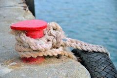 Support rouge sur le pilier avec une corde et un pneu Photo stock