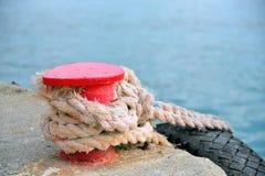 Support rouge sur le pilier avec une corde et un pneu Photos libres de droits