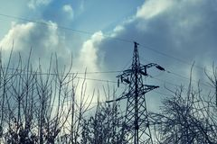 Support or tower power lines against the dark sky and tree branches. stock image