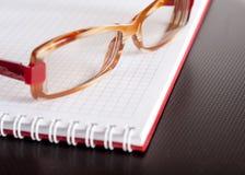 Support unique derrière le bloc-notes et les lunettes photos stock